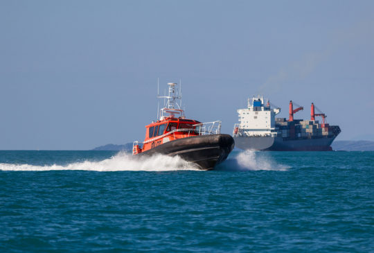 Ocean pilot boat with a large container ship in the background Auckland New Zealand